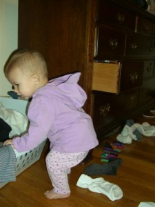 Josie putting socks in the laundry