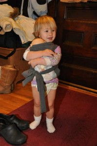 Josie carrying her baby, in old style diaper
