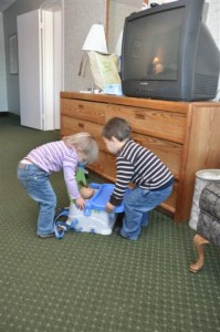 Josie and Zach working together to buckle baby into the high chair