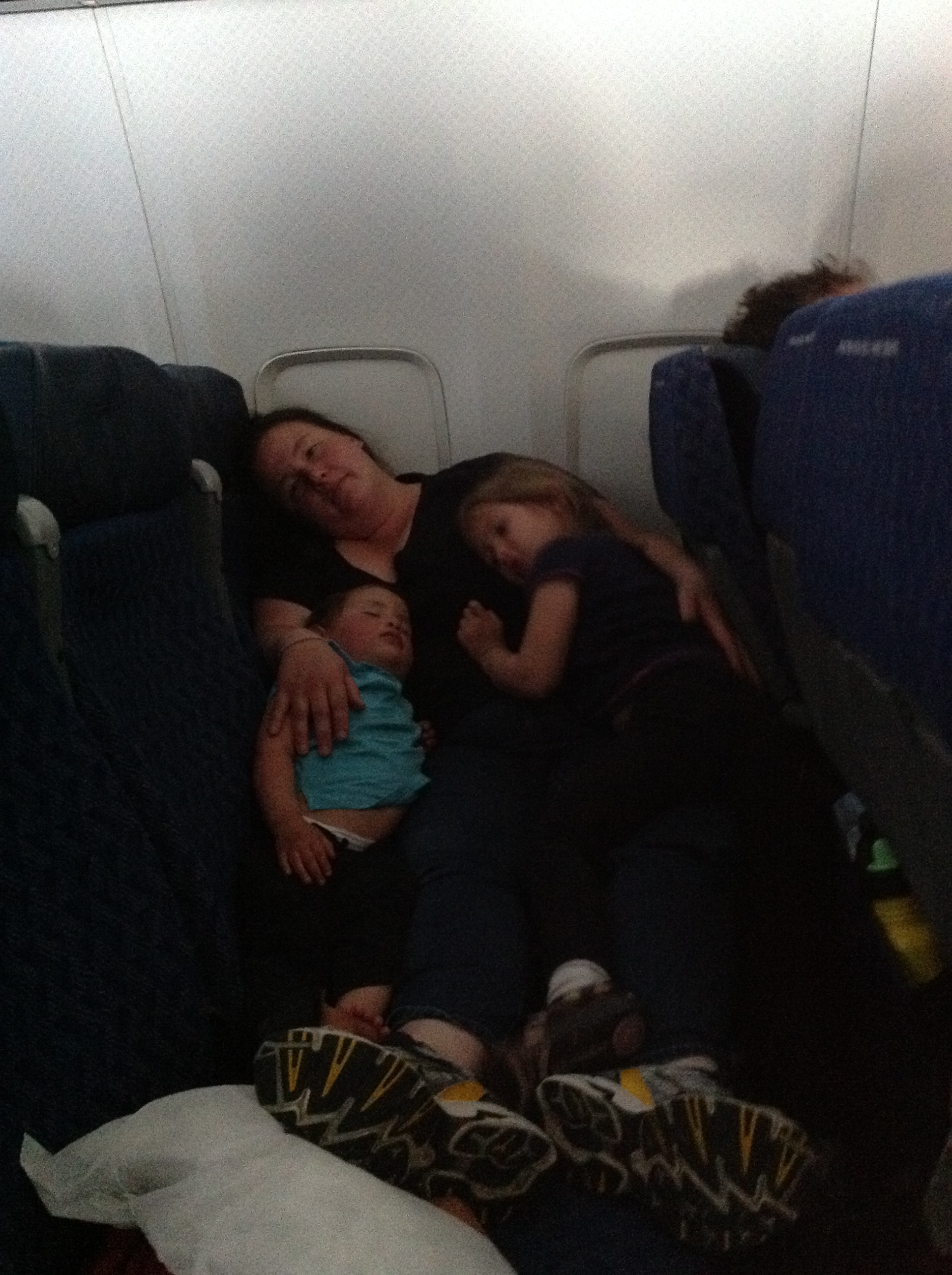 Girls sleeping on Jen on the plane ride home