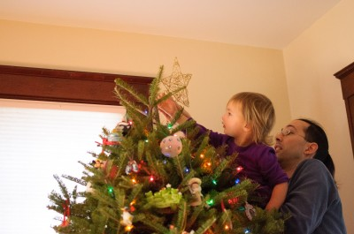 Celia putting the star on the tree
