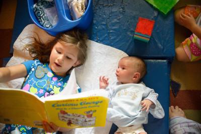 Josie reading to Ewan while Celia plays Magnatiles